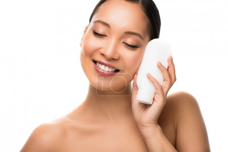 Photo pour Sourire asiatique femme avec les yeux fermés tenant bouteille de lotion, isolé sur blanc - image libre de droit