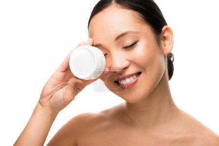 Photo pour Attrayant asiatique fille avec les yeux fermés tenant crème cosmétique, isolé sur blanc - image libre de droit