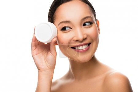 Photo for Happy asian woman holding face cream, isolated on white - Royalty Free Image