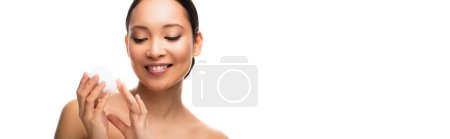 Photo for Smiling asian woman holding face cream, isolated on white - Royalty Free Image