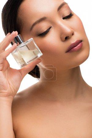 Photo pour Femme asiatique tendre avec les yeux fermés retenant le parfum, d'isolement sur le blanc - image libre de droit