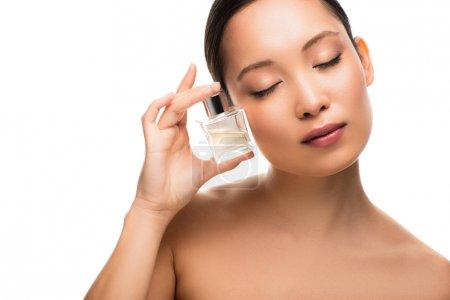 Photo pour Femme asiatique attirante tendre avec les yeux fermés retenant la bouteille de parfum, d'isolement sur le blanc - image libre de droit