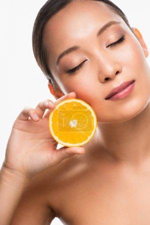 Photo pour Belle femme asiatique tendre avec les yeux fermés retenant l'orange, d'isolement sur le blanc - image libre de droit