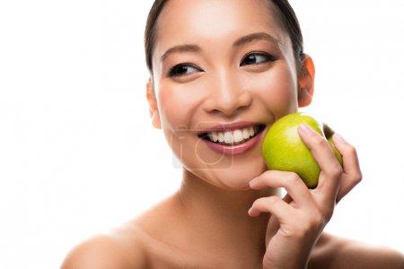 lächelnde Asiatin mit frischem grünen Apfel, isoliert auf weiß