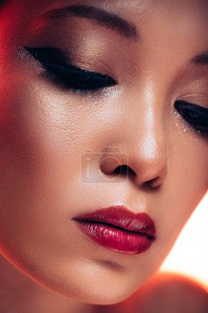 Photo for Attractive asian young woman with makeup in red light - Royalty Free Image