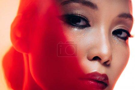 Photo pour Femme asiatique parfaite avec le maquillage dans la lumière rouge - image libre de droit