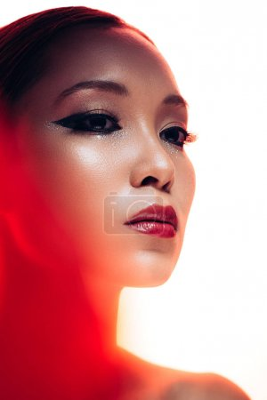 Foto de Beautiful asian woman in red light, isolated on white - Imagen libre de derechos