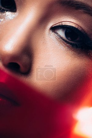 Photo for Close up of asian girl with makeup in red light, toned picture - Royalty Free Image