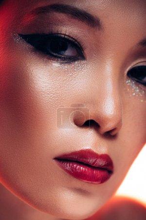 Photo pour Belle jeune femme asiatique jeune dans la lumière rouge, image tonique - image libre de droit