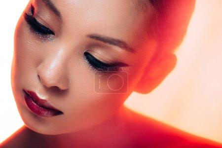 Foto de Beautiful asian woman in red light, toned picture - Imagen libre de derechos