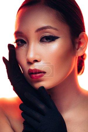 Photo pour Femme asiatique dans des gants noirs avec le maquillage dans la lumière rouge, d'isolement sur le blanc - image libre de droit