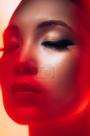 Photo pour Fermez-vous vers le haut de la fille asiatique attirante avec le maquillage dans la lumière rouge - image libre de droit