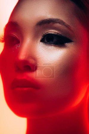Photo pour Fermez-vous vers le haut de la belle fille asiatique avec le maquillage dans la lumière rouge - image libre de droit