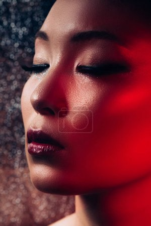 Photo for Close up of sensual asian girl with makeup on closed eyes in red light - Royalty Free Image