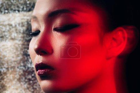Photo pour Fermez-vous vers le haut de la fille asiatique sexy avec les yeux fermés dans la lumière rouge - image libre de droit