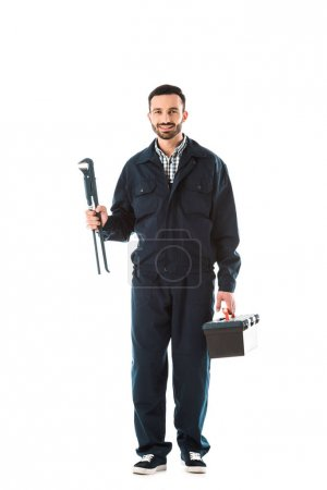 Photo for Happy plumber in overalls holding toolbox and adjustable wrench while smiling at camera isolated on white - Royalty Free Image