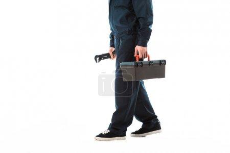 Photo pour Vue recadrée du plombier dans des salopettes tenant la boîte à outils et la clé réglable isolée sur le blanc - image libre de droit