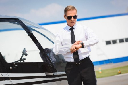 Photo for Pilot in formal wear adjusting watch near helicopter - Royalty Free Image