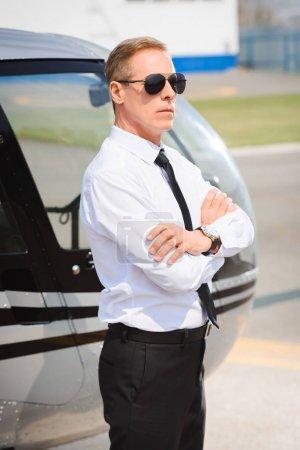 Photo pour Pilote en lunettes de soleil et l'usure formelle avec des bras croisés près de l'hélicoptère - image libre de droit