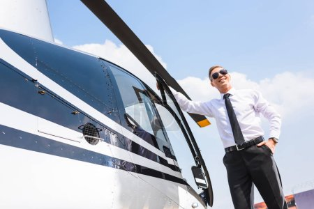Photo for Handsome Pilot in formal wear and sunglasses smiling near helicopter - Royalty Free Image