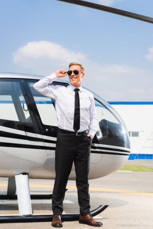 Photo for Handsome Pilot in formal wear adjusting sunglasses and smiling near helicopter - Royalty Free Image