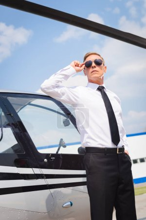 Photo for Pilot in formal wear adjusting sunglasses near helicopter - Royalty Free Image