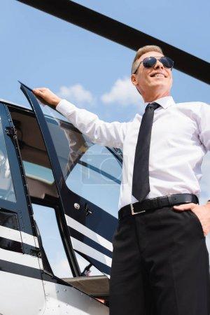 Photo pour Pilote souriant dans l'usure formelle et les lunettes de soleil ouvrant la porte de l'hélicoptère - image libre de droit