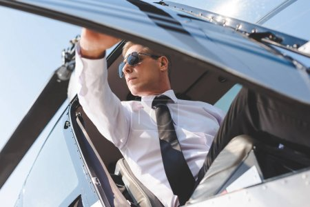 Photo for Handsome Pilot in sunglasses and formal wear opening door while sitting in helicopter cabin - Royalty Free Image