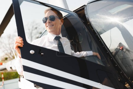 Photo pour Sourire mature pilote dans l'usure formelle séance ouverture porte de l'hélicoptère - image libre de droit