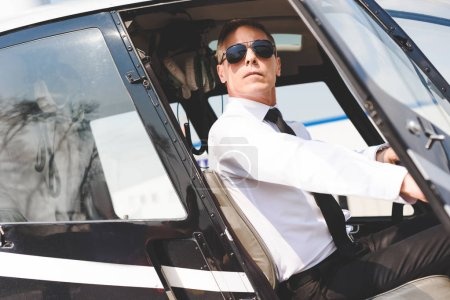 Photo for Confident Pilot in sunglasses and formal wear sitting in helicopter cabin - Royalty Free Image