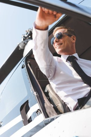 Photo for Smiling Pilot in sunglasses and formal wear sitting in helicopter cabin and opening door - Royalty Free Image