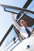 """Постер, картина, фотообои """"низкий угол зрения пилота в солнцезащитных очках и формальной одежды, сидя в кабине вертолета и открывая дверь"""""""