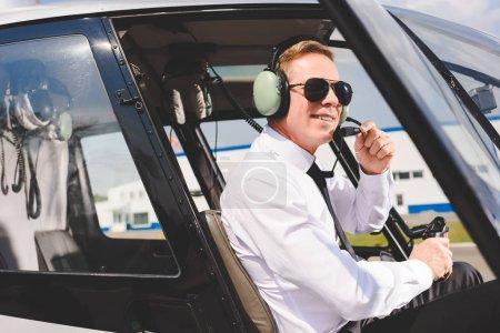 Photo pour Pilote souriant en lunettes de soleil et casque assis dans la cabine de l'hélicoptère - image libre de droit
