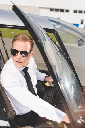 Photo for Handsome Pilot in sunglasses and formal wear sitting in helicopter cabin and opening door - Royalty Free Image