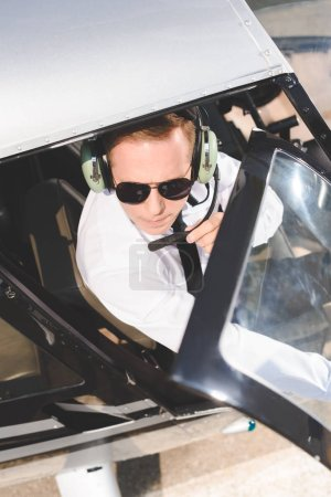 Photo for Top view of Pilot in sunglasses and headset with microphone sitting in helicopter cabin - Royalty Free Image