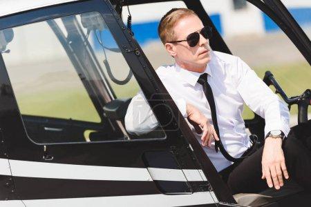 Photo pour Grave mature pilote dans l'usure formelle assis dans la cabine de l'hélicoptère - image libre de droit