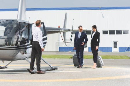 Photo for Business partners in formal wear with suitcases near pilot and helicopter - Royalty Free Image