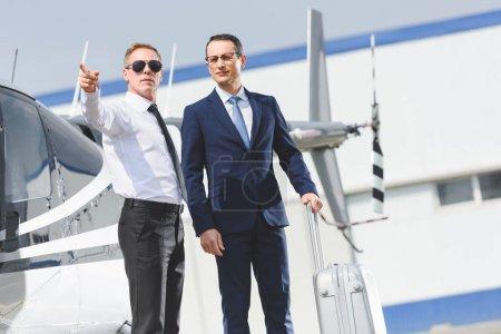 Photo pour Pilote dans l'usure formelle pointant avec le doigt et l'homme d'affaires avec la valise près d'hélicoptère - image libre de droit