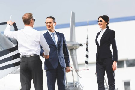 Photo for Businessman with luggage shaking hands with pilot near helicopter and businesswoman - Royalty Free Image