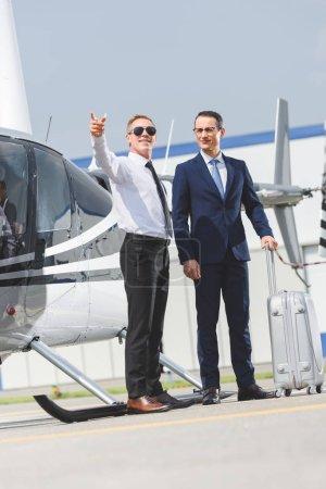 Foto de Piloto en uso formal apuntando con el dedo y el empresario con el equipaje cerca del helicóptero - Imagen libre de derechos