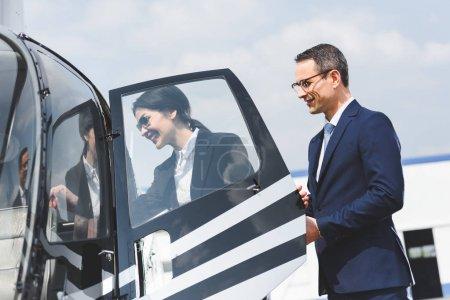 Photo pour Porte ouverte d'homme d'affaires d'hélicoptère pour la femme d'affaires souriante - image libre de droit
