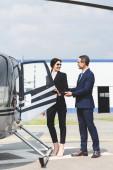"""Постер, картина, фотообои """"бизнесмен в формальной одежде открытия двери вертолета для бизнес-леди"""""""