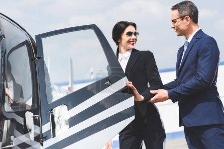 Photo pour Porte ouverte d'homme d'affaires d'hélicoptère pour la belle femme d'affaires - image libre de droit