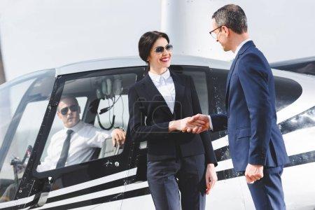 Photo pour Hommes d'affaires en costumes serrer la main près de l'hélicoptère avec pilote - image libre de droit