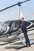 """Постер, картина, фотообои """"Пилот в формальной одежде сидит в вертолете в то время как бизнесмен открывает дверь"""""""