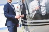 """Постер, картина, фотообои """"обрезанный вид пилота, сидящего в вертолете в то время как бизнесмен, открывая дверь"""""""