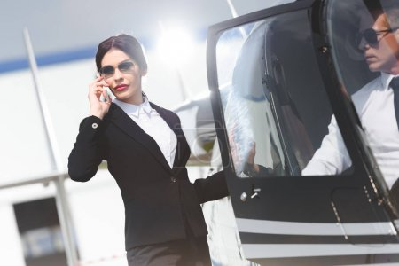 Photo for Businesswoman in formal wear talking on smartphone near helicopter with pilot - Royalty Free Image