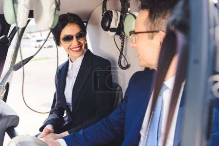 Photo for Businesswoman and businessman in formal wear sitting in helicopter cabin - Royalty Free Image
