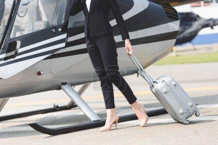 Photo pour Vue recadrée de femme d'affaires dans l'usure formelle avec la valise près de l'hélicoptère - image libre de droit