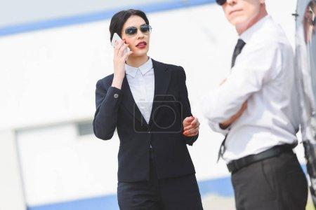 selective focus of businesswoman talking on smartphone near man